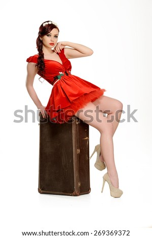 Beautiful woman in a red dress  with retro suitcase posing on a white background   - stock photo