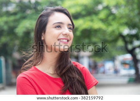 Beautiful woman in a red shirt outdoor in a park - stock photo