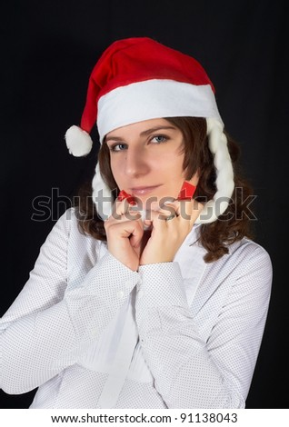 beautiful woman in a Santa Claus hat on black background - stock photo
