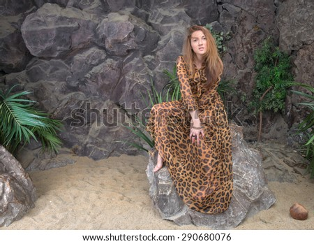 Beautiful woman in a spotted dress in the form of a panther