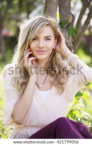 Beautiful woman in a spring garden with blooming lilacs - stock photo