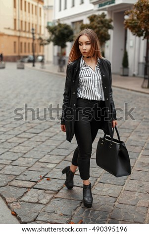 Beautiful woman in a stylish black coat, fashionable autumn clothes with a bag near buildings in the city
