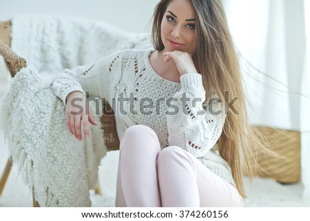 Beautiful woman in a sweater at home - stock photo