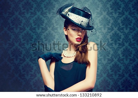 Beautiful woman in a vintage hat over a fashion background - stock photo