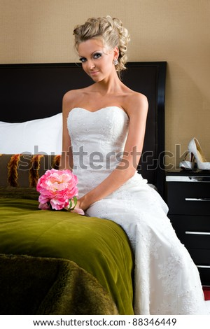 Beautiful woman in a wedding dress. She is in the bedroom with luxurious interior - stock photo