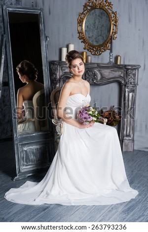 Beautiful woman in a wedding dress sit in a chair - stock photo