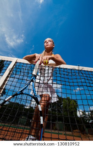 Beautiful woman in a white suit and tennis racket in her hands standing behind the net. Bottom view - stock photo