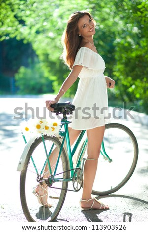 Beautiful woman in a white summer dress standing and holding on old bike - stock photo