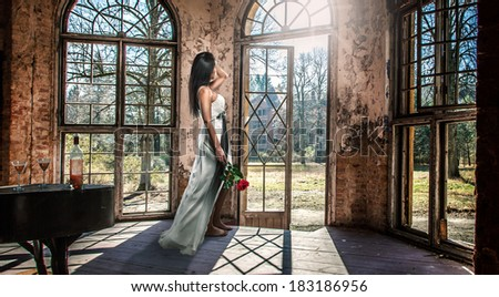 Beautiful woman in a white wedding dress and a rose - stock photo