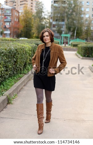 Beautiful woman in autumn street - stock photo