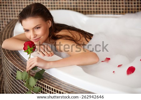 Beautiful Woman in bath with rose. Body care. - stock photo