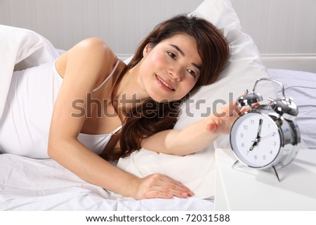 Beautiful woman in bed reaching for alarm clock - stock photo