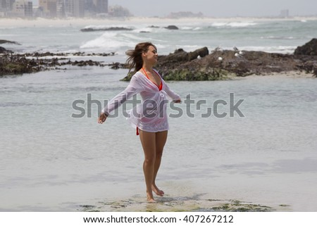 Beautiful woman in bikini and shirt with her arms outstretched enjoying the beach - stock photo