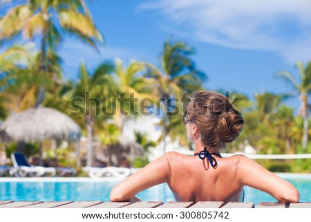 Beautiful woman in bikini relaxing by the tropical  pool - stock photo
