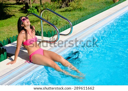 Beautiful woman in bikini sitting at poolside enjoying her summer  vacation.  Happy girl wearing sunglasses with feet under swimming pool water. - stock photo