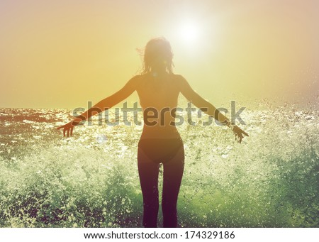 Beautiful Woman in Bikini Standing in the Sea Waves and Enjoying Sunshine with Open Arms - stock photo