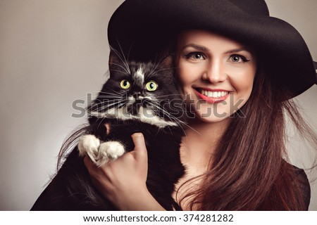 Beautiful woman in black dress and hat with cat  - stock photo