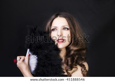 Beautiful woman in black dress holding fan of feathers on dark studio background - stock photo