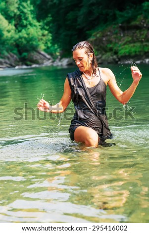 Beautiful woman in black dress in a river