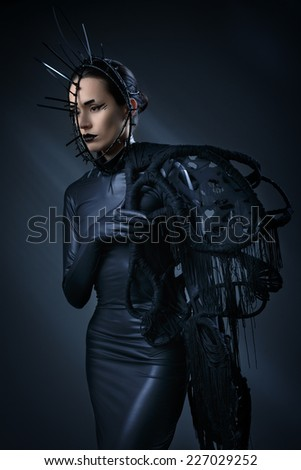 Beautiful woman in black Gothic dress. The face wearing a mask. Studio photography. Mystical images. Halloween style.