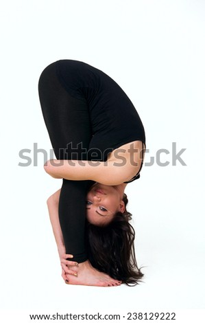 Beautiful woman in black sportswear doing yoga uttanasana or standing forward bend in studio. Over white background - stock photo