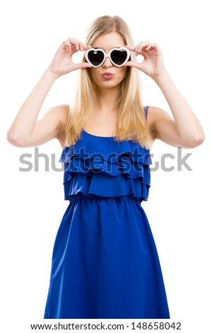 Beautiful woman in blue dress using sunglasses with a hearth shape, isolated over white background - stock photo