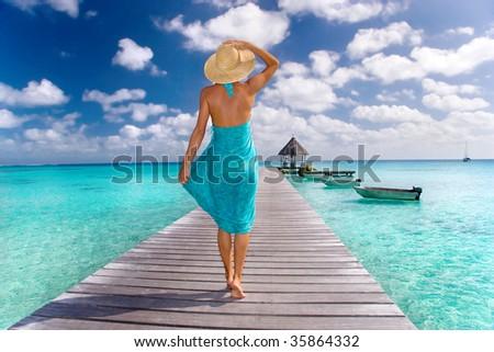 beautiful woman in blue sarong walks down resort pier - stock photo