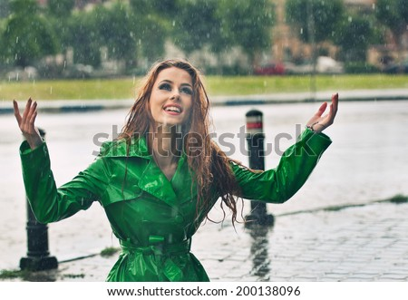 Beautiful woman in bright green coat posing in the rain. Happy redhead enjoying the rain drops in the park, outdoor shot. Beautiful red hair girl relaxing in a rainy summer day. Attractive female. - stock photo