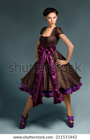 Beautiful woman in brown and purple vintage dress - stock photo