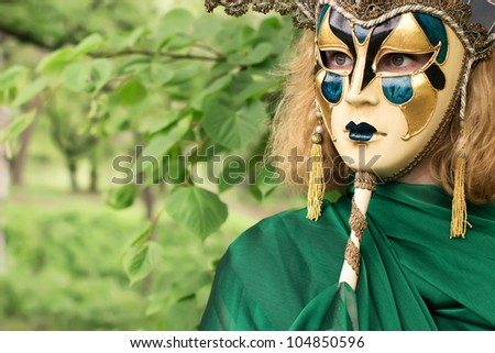 Beautiful woman in carnival mask over foliage background - stock photo