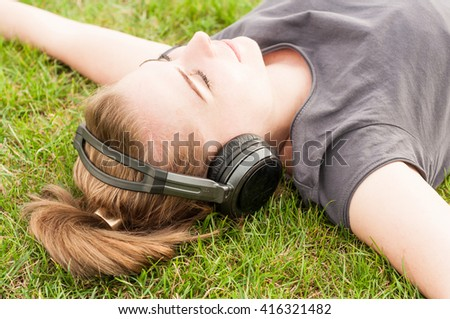 Beautiful woman in closeup lying on grass and listen music as relaxation and freetime concept - stock photo