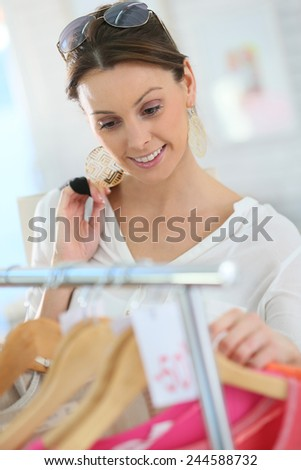 Beautiful woman in clothing store during summer sales