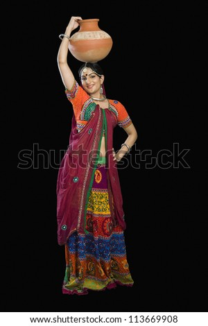 Beautiful woman in colorful lehenga choli carrying water pot