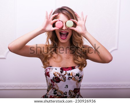 Beautiful woman in colour dress make faces with macaroons in studio - stock photo