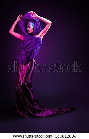 Beautiful woman in creative dress purple light - stock photo