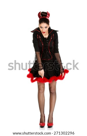 Beautiful woman in devil carnival costume pointing down. - stock photo