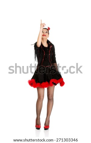 Beautiful woman in devil carnival costume pointing up. - stock photo