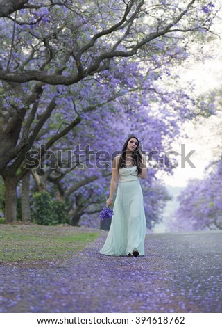 Beautiful woman in dreamy dress holding a bouquet of purple flowers in her hand while walking down a street with lanes of blooming purple Jacaranda trees. - stock photo