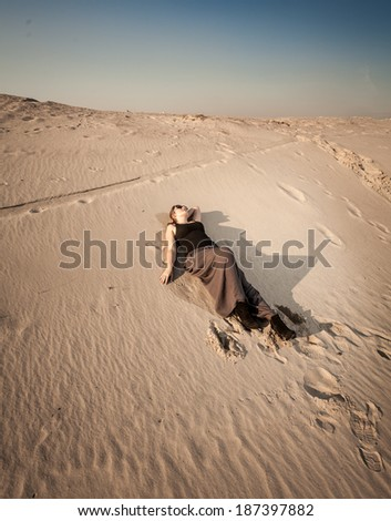 Beautiful woman in dress lying on sand dune at desert