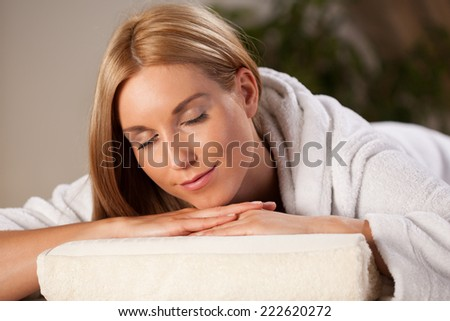 Beautiful woman in dressing gown relaxing in spa - stock photo