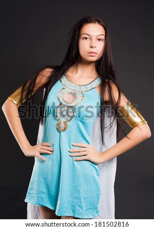 Beautiful woman in egyptian queen costume at black background - stock photo