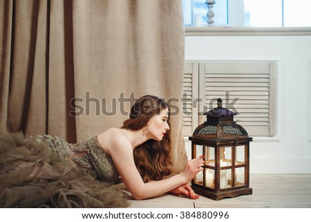 Beautiful Woman in Elegant Dress Looking in Lantern with Candles. Romantic Evening Concept. - stock photo