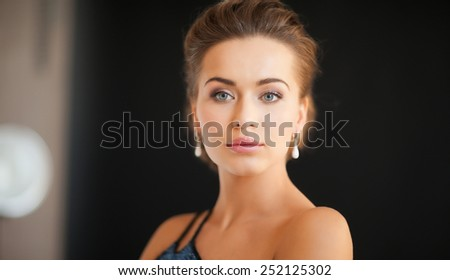 beautiful woman in evening dress wearing diamond earrings - stock photo