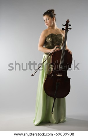 Beautiful woman in evening dress with cello - stock photo