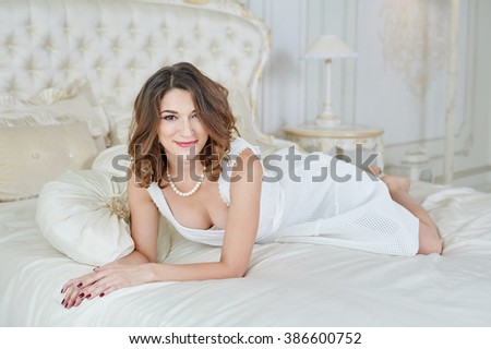 beautiful woman in evening dress with decollete lying on bed