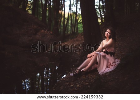 Beautiful woman in fairy forest near a stream - stock photo