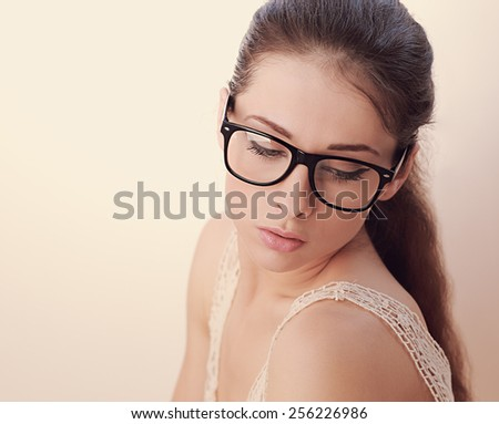 Beautiful woman in fashion glasses looking down. Soft light portrait - stock photo