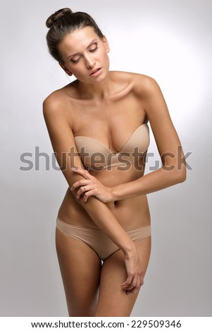 Beautiful woman in flesh color underwear. Studio shooting. - stock photo