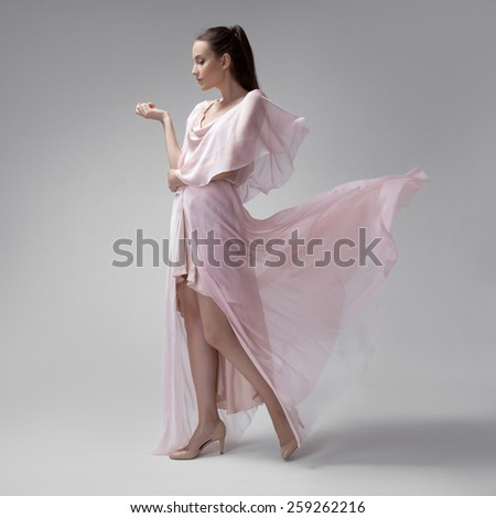 Beautiful woman in fluttering airy pink dress. Gray background. - stock photo