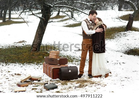Beautiful woman in fur coat leans to her handsome man while they stand behind the suitcases
